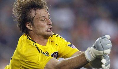 Chicago Fire goalie Andrew Dykstra, top, punches the ball away from the net in front of Dasan Robinson after a shot by the New England Revolution in the second half of an MLS soccer game, Sunday, June 27, 2010, in Foxborough, Mass. The Fire won 1-0. (AP Photo/Michael Dwyer)