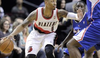 Portland Trail Blazers guard Damian Lillard, left, looks for room to maneuver around Los Angeles Clippers forward Glen Davis during the first half of an NBA basketball game in Portland, Ore., Wednesday, April 16, 2014. (AP Photo/Don Ryan)