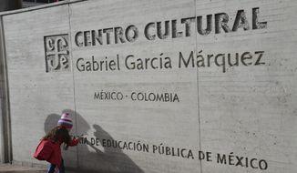A girl touches the sign outside the Gabriel Garcia Marquez cultural center in downtown Bogota, Colombia, Thursday, April 17, 2014. The Colombian Nobel laureate Gabriel Garcia Marquez died in Mexico City on Thursday. (AP Photo/Diana Sanchez)