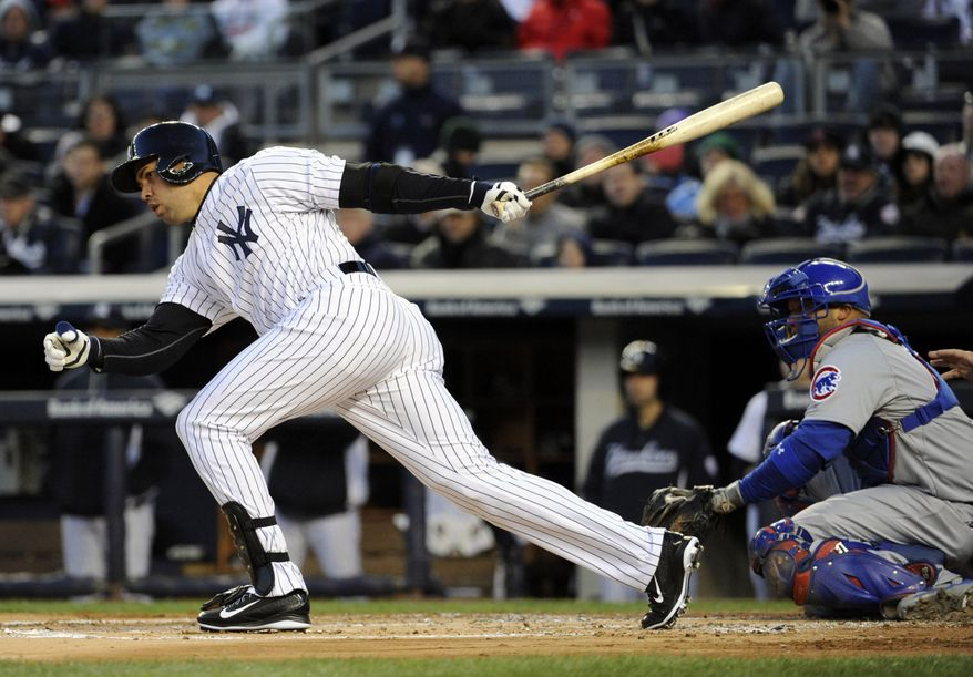 New York Yankees' Carlos Beltran, left, hits a double as Chicago Cubs catcher Welington Castillo, right, looks on during the first inning of Game 2 of an interleague baseball doubleheader on Wednesday, April 16, 2014, at Yankee Stadium in New York. (AP Photo/Bill Kostroun)