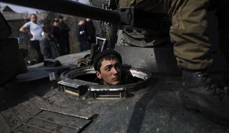 A Ukrainian soldier is seen in a tank of the Ukrainian Army, as they are blocked by people on their way to the town of Kramatorsk on Wednesday, April 16, 2014. Pro-Russian insurgents commandeered six Ukrainian armored vehicles along with their crews and hoisted Russian flags over them Wednesday, dampening the central government's hopes of re-establishing control over restive eastern Ukraine. (AP Photo/Manu Brabo)