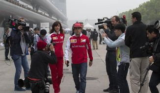 Ferrari driver Fernando Alonso of Spain, center, is surrounded by journalists as he walks on the paddock ahead of Sunday's Chinese Formula One Grand Prix at Shanghai International Circuit in Shanghai, China Thursday, April 17, 2014. (AP Photo/Andy Wong)