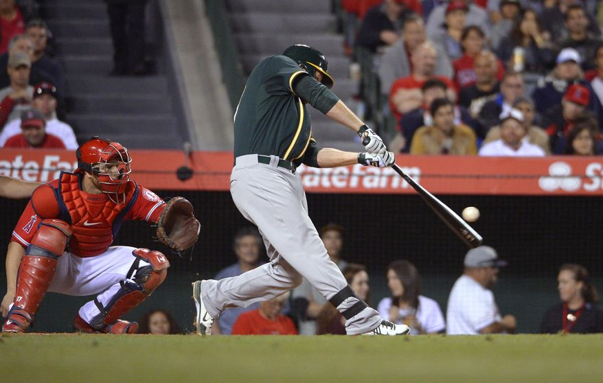 Oakland Athletics' Brandon Moss, right, hits a three-run home run as Los Angeles Angels catcher Chris Iannetta watches during the fourth inning of a baseball game, Wednesday, April 16, 2014, in Anaheim, Calif. (AP Photo/Mark J. Terrill)