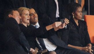 US President  Barack Obama (R) and British Prime Minister David Cameron pose for a picture with Denmark's Prime Minister Helle Thorning Schmidt (C) next to US First Lady Michelle Obama (R) during the memorial service of South African former president Nelson Mandela at the FNB Stadium (Soccer City) in Johannesburg on December 10, 2013. Mandela, the revered icon of the anti-apartheid struggle in South Africa and one of the towering political figures of the 20th century, died in Johannesburg on December 5 at age 95.   AFP PHOTO / ROBERTO SCHMIDT        (Photo credit should read ROBERTO SCHMIDT/AFP/Getty Images)