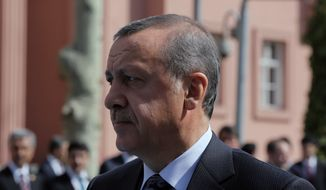 Turkish Prime Minister Recep Tayyip Erdogan walks outside his office in Ankara, Turkey, Thursday, April 17, 2014. Turkey's parliament looks set to pass a bill that increases the powers and immunities of the country's spy agency. It is the latest in a string of moves critics say is undermining democracy in the country that is a candidate to join the European Union. The bill, expected to be voted on Thursday, gives the National Intelligence Agency greater eavesdropping and operational powers and increases its immunities and abilities to keep tabs on citizens. Journalists publishing classified documents would face prison terms. (AP Photo/Burhan Ozbilici)