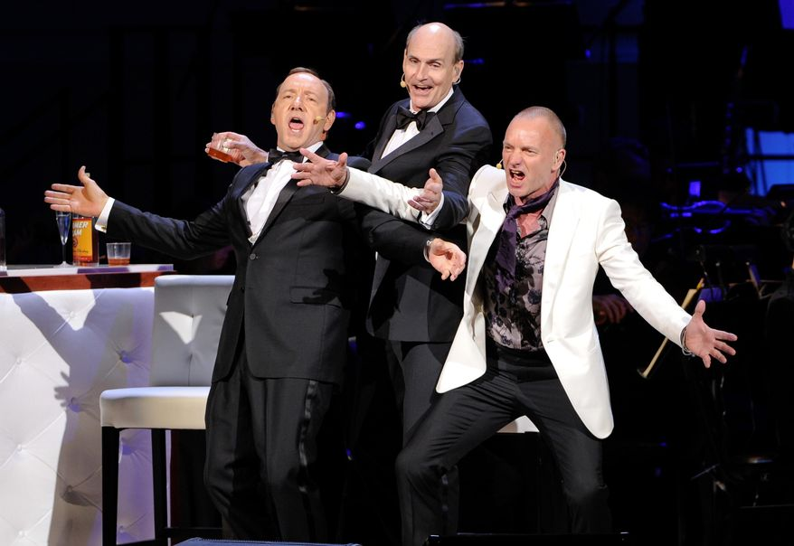 Actor Kevin Spacey, left, performs with singers James Taylor and Sting, right, at the 25th Anniversary Rainforest Fund benefit concert at Carnegie Hall on Thursday, April 17, 2014 in New York. (Photo by Evan Agostini/Invision/AP)
