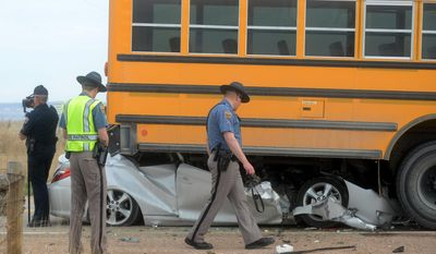 Colorado State Troopers and a Larimer County Sheriff Deputy investigate an accident on Larimer County Road 82, where a car rear-ended a school bus that had stopped to pick up students Friday, April 18, 2014, in Wellington, Colo. A Poudre school official says three children have been injured in the accident involving a school bus and a passenger vehicle north of Fort Collins. (AP Photo/The Coloradoan, V. Richard Haro)