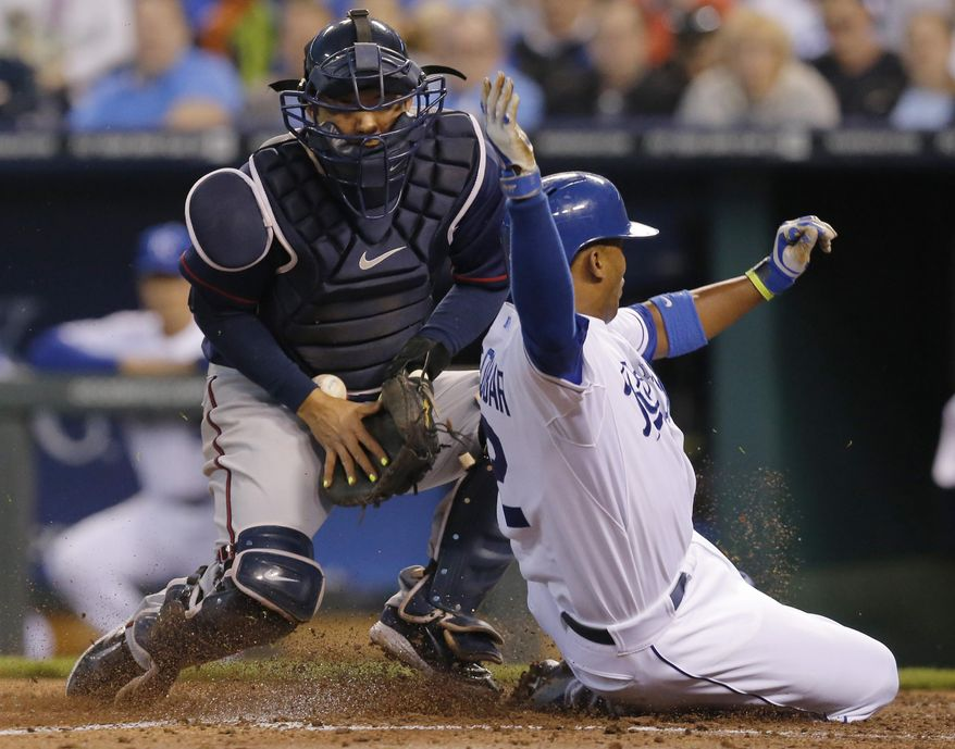 Kansas City Royals' Alcides Escobar (2) slides safely past Minnesota Twins catcher Kurt Suzuki during the third inning of a baseball game at Kauffman Stadium in Kansas City, Mo., Friday, April 18, 2014. Escobar scored on a single hit by teammate Omar Infante. (AP Photo/Orlin Wagner)
