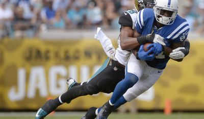 In this Sept. 29, 2013, photo, Indianapolis Colts wide receiver Reggie Wayne (87) catches a pass in front of Jacksonville Jaguars free safety Josh Evans during an NFL football game in Jacksonville, Fla.  Wayne is trying to return from a torn anterior cruciate ligament in his right knee. (AP Photo/Phelan M. Ebenhack)
