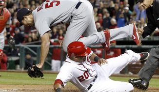 Washington Nationals' Ian Desmond (20) scores as St. Louis Cardinals starting pitcher Michael Wacha cannot handle the throw from catcher Yadier Molina after the past ball during the seventh inning of a baseball game at Nationals Park, Friday, April 18, 2014, in Washington. Nationals' Danny Espinosa also scored. The Nationals won 3-1. (AP Photo/Alex Brandon)