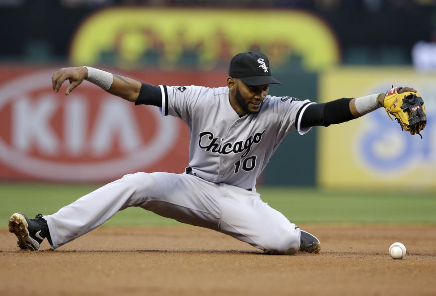 Chicago White Sox shortstop Alexei Ramirez slips while trying to field an RBI single by Texas Rangers' Kevin Kouzmanoff in the first inning of a baseball game, Friday, April 18, 2014, in Arlington, Texas.  Elvis Andrus scored on the hit. (AP Photo/Tony Gutierrez)