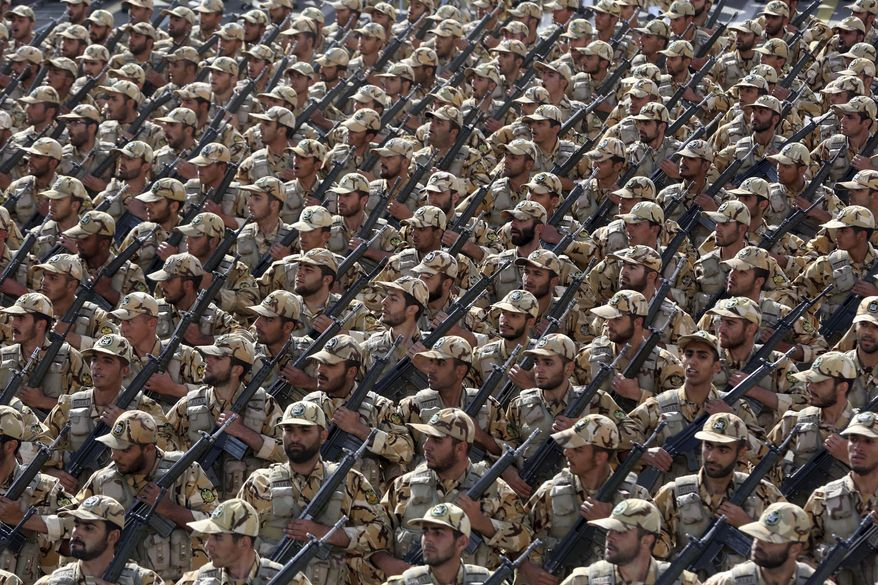 Iranian army troops march in a parade marking National Army Day in front of the mausoleum of the late revolutionary founder Ayatollah Khomeini just outside Tehran, Iran, Friday, April 18, 2014. Ahead of the parade, Iran's President Hassan Rouhani underscored his moderate policies and outreach to the West in a speech. (AP Photo/Vahid Salemi)