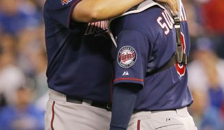 Minnesota Twins starting pitcher Ricky Nolasco, left, talks with catcher Kurt Suzuki, right, after giving up a run in the third inning of a baseball game against the Kansas City Royals at Kauffman Stadium in Kansas City, Mo., Friday, April 18, 2014. (AP Photo/Orlin Wagner)