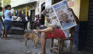 A man reads a newspaper fronted with the news of the death of Nobel laureate Gabriel Garcia Marquez, in Aracataca, the town were he was born in Colombia's Caribbean coast, Friday, April 18, 2014. Garcia Marquez died in Mexico City on Thursday April 17. (AP Photo/Ricardo Mazalan)