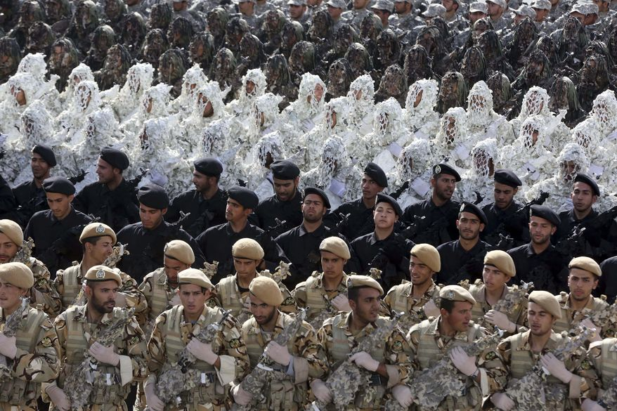 Iranian army troops march in a parade, some of them wearing ghilli suits, marking National Army Day in front of the mausoleum of the late revolutionary founder Ayatollah Khomeini just outside Tehran, Iran, Friday, April 18, 2014. Ahead of the parade Iran's President Hassan Rouhani underscored his moderate policies and outreach to the West in a speech. (AP Photo/Vahid Salemi)