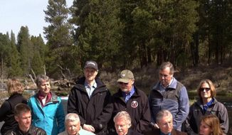 In ceremonies outside Chiloquin, Ore. on Friday, April 18, 2014, Gov. John Kitzhaber, center foreground, prepares to sign an agreement between Upper Klamath Basin cattle ranchers and the Klamath Tribes to share access to rivers and cooperate on restoring fish sacred to the tribes. He is flanked by representatives of the ranchers and the tribes. Behind them are Senators Ron Wyden, third from left background, and Jeff Merkley, second from right, and representatives of the Obama administration. (AP Photo/U.S. Fish and Wildlife Service, Matt Baun)