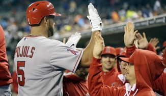 Los Angeles Angels' Albert Pujols (5) is congratulated in the dugout after hitting a three-run home run during the sixth inning of a baseball game against the Detroit Tigers in Detroit, Friday, April 18, 2014. (AP Photo/Carlos Osorio)