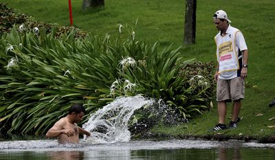 Pablo Larrazabal, left, of Spain, jumps into a lake after being attacked by a swarm of hornets during the second round of the Malaysian Open golf tournament at Kuala Lumpur Golf and Country Club in Kuala Lumpur, Malaysia, Friday, April 18, 2014. (AP Photo/Joshua Paul)