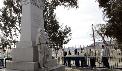 FILE - This  Feb. 28, 2008 file photo shows visitors at the monument to those killed in the Ludlow Massacre at the site near Ludlow, Colo. Sunday, April 20, 2014 marks the 100th anniversary of the Ludlow Massacre where two women and 11 children were killed in a fire during a battle between striking coal miners and Colorado National Guard. (AP Photo/David Zalubowski, File)