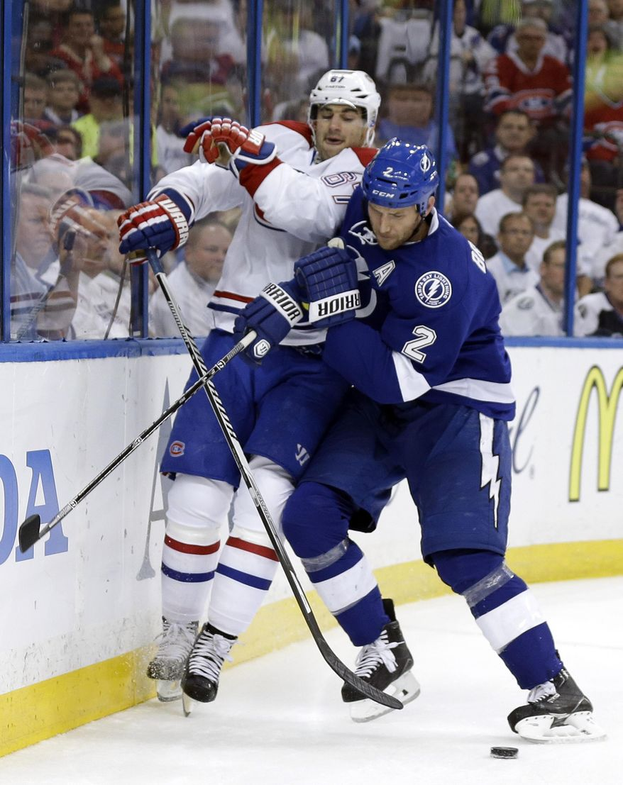 Tampa Bay Lightning defenseman Eric Brewer (2) checks Montreal Canadiens left wing Max Pacioretty (67) into the boards during the first period of Game 2 of a first-round NHL hockey playoff series on Friday, April 18, 2014, in Tampa, Fla. (AP Photo/Chris O'Meara)