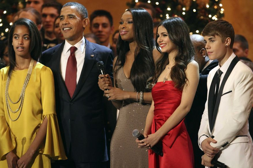 """From left, Malia Obama, President Barack Obama, and performers Jennifer Hudson, Victoria Justice, and Justin Bieber, stand on stage before singing """"Hark! The Herald Angels Sing"""" at the annual Christmas in Washington taping at the National Building Museum in Washington, Sunday, Dec. 11, 2011. (AP Photo/Jacquelyn Martin)"""