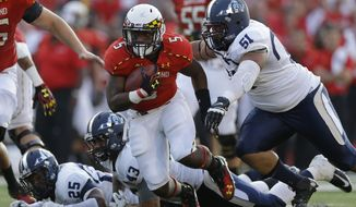 Maryland running back Albert Reid, center, rushes past Old Dominion defenders Andre Simmons (25), Caleb Taylor (43) and Malik Gumbs (51) in the second half of an NCAA college football game in College Park, Md., Saturday, Sept. 7, 2013. Maryland won 47-10. (AP Photo/Patrick Semansky)