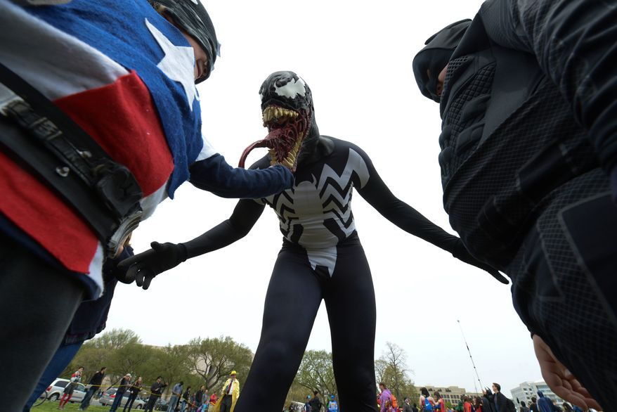 Ricky Tomlin, 42, portraying Venom Symbiote, has a little fun showing off his costume with Pilot Jack Henderson (Captain America) , 5 of York, Pa, left, and Isaac Holliday (Batman), 8 of Grantsville, Md during Awesome Con D.C. and the Museum of Science Fiction attempt to break a world record for the largest gathering of people dressed as comic book characters at the U.S. Capitol Reflecting Pool on Friday, April 18. The current record holder is China; which stands at 1,530 people, set on April 19, 2011 at the opening ceremony of the International Animation CCJOY LAND. Awesome Con D.C. and the Museum of Science Fiction didn't come close with only 237 people showing up. (Khalid Naji-Allah/ Special to The Washington Times)