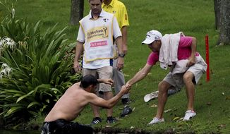 Pablo Larrazabal, left, of Spain, is pulled out of a lake after being attacked by a swarm of hornets during the second round of the Malaysian Open golf tournament at Kuala Lumpur Golf and Country Club in Kuala Lumpur, Malaysia, Friday, April 18, 2014. (AP Photo/Joshua Paul)
