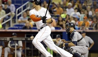 Miami Marlins' Giancarlo Stanton, left, watches after hitting an RBI-single to score Marcell Ozuna during the first inning of an interleague baseball game against the Seattle Mariners, Friday, April 18, 2014, in Miami. Mariners catcher Mike Zunino, right, looks on. (AP Photo/Lynne Sladky)