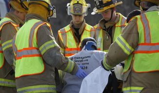 In this April 17, 2014 photo, firefighters attend to an injured person near Comstock Township, Mich., following two accidents. A western Michigan volunteer firefighter responding to a head-on crash in Kalamazoo County struck another vehicle, fatally injuring the driver. (AP Photo/Kalamazoo Gazette-MLive Media Group, Mark Bugnaski) PHOTO ALL LOCAL TV OUT; LOCAL TV INTERNET OUT