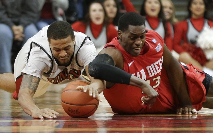 ADVANCE FOR WEEKEND EDITIONS APRIL 20-21 - FILE - In this Feb. 16, 2013, file photo, UNLV's Bryce Dejean-Jones, left, and San Diego State's DeShawn Stephens dive for a loose ball in the second half of an NCAA college basketball game in Las Vegas. Division I coaches are realizing that they can win both now and later with transfers, who are suddenly viewed more like shiny new toys than damaged goods. A recent surge in player movement has turned the once-sleepy late signing period, which starts on Wednesday and runs through May 21, into a month-long free agent frenzy that's transformed the game.  (AP Photo/Julie Jacobson, File)