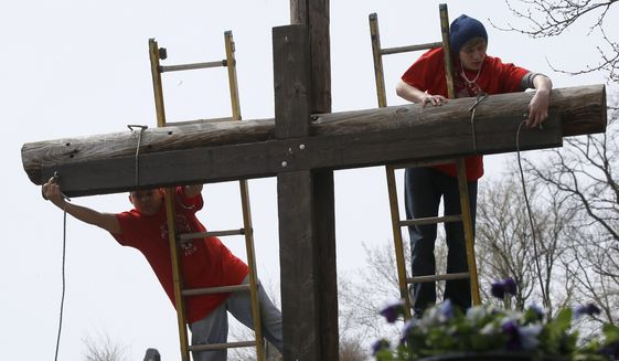 "Volunteers tie the wooden cross that was carried through the streets of Etna, Pa., a Pittsburgh suburb, to the larger cross in the cemetery where their annual ""Drama of The Cross,"" service was done on Good Friday, Friday, April 18, 2014. (AP Photo/Keith Srakocic) ** FILE **"