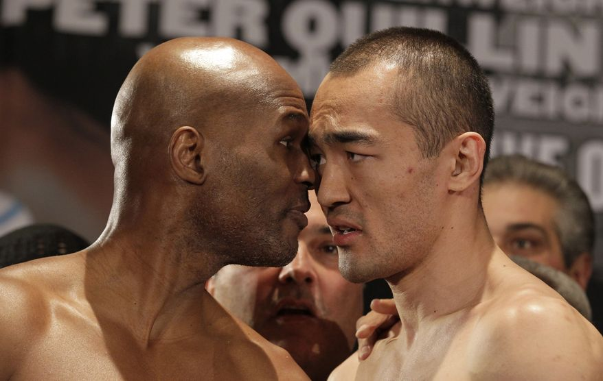 IBF light heavyweight boxing champion Bernard Hopkins, left, faces off with WBA and IBA light heavyweight boxing champion Beibut Shumenov, of Kazakhstan, after a weigh-in Friday, April 18, 2014, in Washington. Hopkins will fight Shumenov in a unification title match Saturday, April 19, 2014, in Washington. (AP Photo/Luis M. Alvarez)