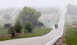 FILE - This April 19, 2012 file photo shows a truck traveling along highway 14, several miles north of Neligh, Neb. near the proposed new route for the Keystone XL pipeline. The US is extending indefinitely the amount of time federal agencies have to review the Keystone XL pipeline, the State Department said Friday, likely punting the decision over the controversial oil pipeline until after the midterm elections. The State Department didn't say how much longer it will grant agencies to weigh in, but cited a recent decision by a Nebraska judge that overturned a state law that allowed the pipeline's path through the state, prompting uncertainty and an ongoing legal battle. Nebraska's Supreme Court isn't expected to rule for another several months and there could be more legal maneuvering after that, potentially freeing President Barack Obama to avoid making a final call on the pipeline until after the election in November.  (AP Photo/Nati Harnik, File)