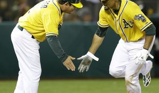 Oakland Athletics' Coco Crisp, right, is congratulated by third base coach Mike Gallego after Crisp hit a home run in the fifth inning of a baseball game off Houston Astros' Paul Clemens Friday, April 18, 2014, in Oakland, Calif. (AP Photo/Ben Margot)