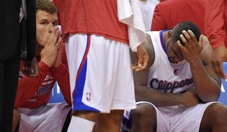 Los Angeles Clippers' Blake Griffin, left, looks on from the bench as Glen Davis rubs his head during the second half in Game 1 of an opening-round NBA basketball playoff series, Saturday, April 19, 2014, in Los Angeles. The Warriors won 109-105. (AP Photo/Mark J. Terrill)