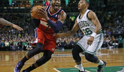 Washington Wizards guard John Wall (2) drives against Boston Celtics guard Phil Pressey (26) during the first quarter of an NBA basketball game in Boston, Wednesday, April 16, 2014. (AP Photo/Elise Amendola)