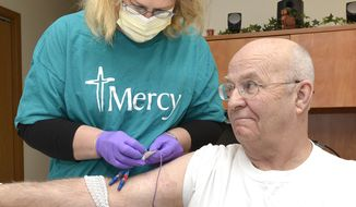 FOR RELEASE SATURDAY, APRIL 19, 2014, AT 12:01 A.M. CDT - In this Jan. 27, 2014 photo, Denise Berger, a home health care nurse with  Mercy Medical Center-Sioux City, changes the dressing on a central catheter line for patient Gary Kelley at Kelley's Sioux City, Iowa home. (AP Photo/The Sioux City Journal, Tim Hynds)