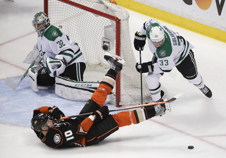 Anaheim Ducks' Corey Perry (10) falls to the ice after he was pushed by Dallas Stars' Alex Goligoski (33) as Stars goalie Kari Lehtonen, of Finland, watches during the first period in Game 2 of the first-round NHL hockey Stanley Cup playoff series, Friday, April 18, 2014, in Anaheim, Calif. (AP Photo/Jae C. Hong)