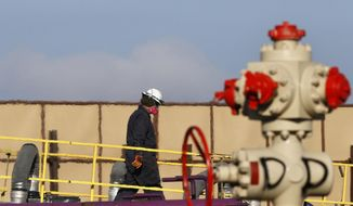 ** FILE ** This March 25, 2014, file photo shows heat from machinery distorts the air as a worker watches over a hydraulic fracturing operation at an Encana Corp. gas well near Mead, Colo. (AP Photo/Brennan Linsley, File)