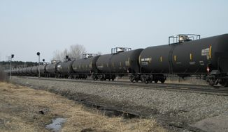 In this April 15, 2014 photo, an oil-tank train operated by Burlington Northern Santa Fe Corp., based in Fort Worth, Texas, cruises east alongside U.S. 10, a few miles outside of Staples, Minn. Multiple BNSF oil-tank trains travel through Staples every day, pulling about 110 tanks, sometimes more, of highly volatile crude from the Bakken shale fields in North Dakota to refineries east and south of Minnesota. (AP Photo/Mike Cronin)