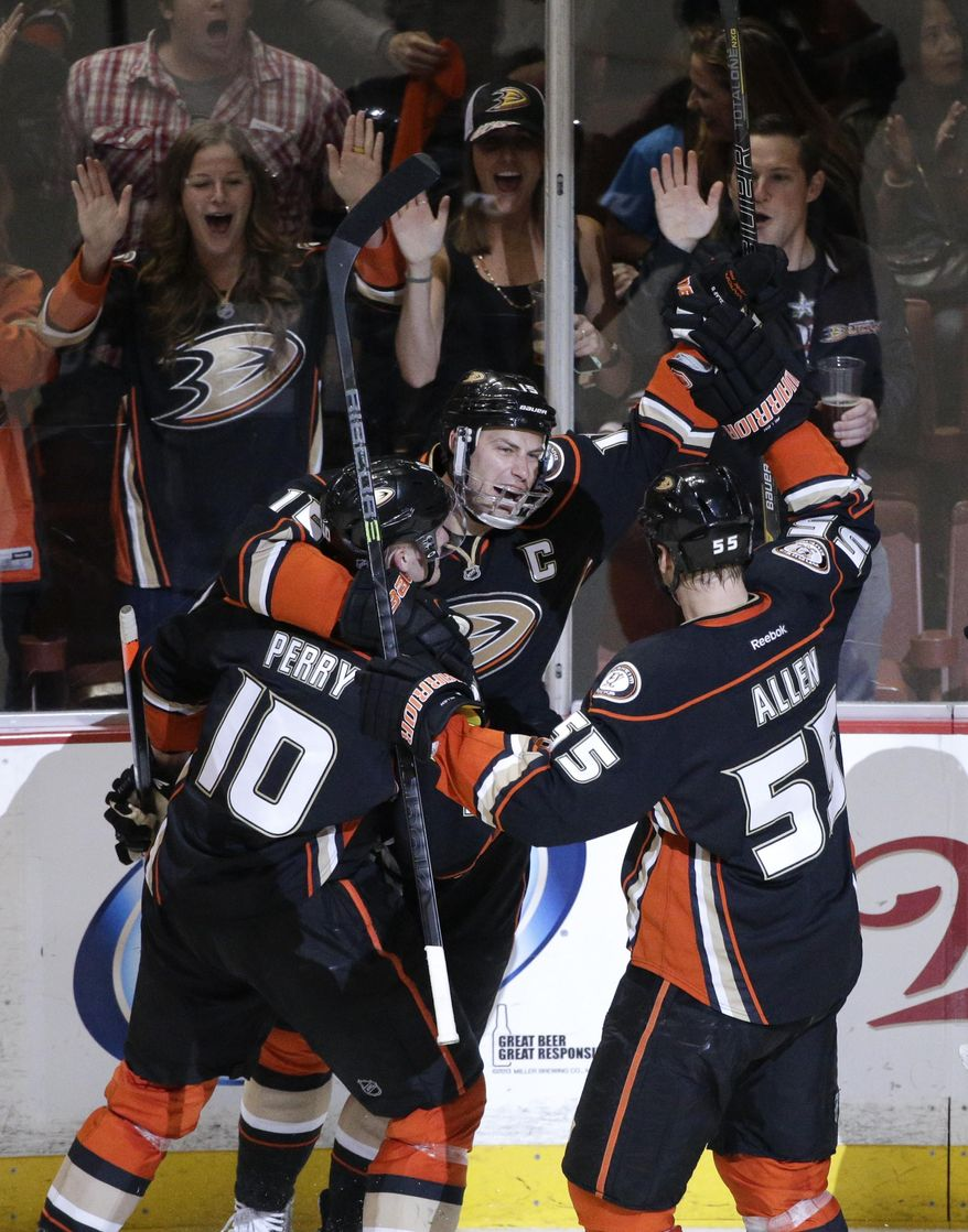 Anaheim Ducks' Ryan Getzlaf (15) celebrates his goal with Corey Perry (10) and Bryan Allen (55) during the first period in Game 2 of the first-round NHL hockey Stanley Cup playoff series against the Dallas Stars on Friday, April 18, 2014, in Anaheim, Calif. (AP Photo/Jae C. Hong)