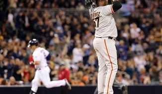 San Francisco Giants relief pitcher Juan Gutierrez looks to the outfield after giving up a solo home run to San Diego Padres' Yasmadi Grandal in the eighth inning of a MLB baseball game Friday, April 18, 2014, in San Diego. San Diego Padres won 2-1. (AP Photo/Don Boomer)