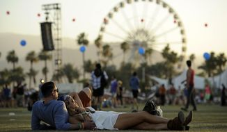 FILE - In this Sunday, April 13, 2014 file photo, Coachella festival goers Justin Gibbs and Olivia Hansen of Los Angeles relax on the Empire Polo Field during the third day of the 2014 Coachella Music and Arts Festival in Indio, Calif.  The Coachella crowd may be there to listen to music under the hot desert sun, but the retailers are there for the celebs and the crowd, which is young, hip and with money to spend.  (Photo by Chris Pizzello/Invision/AP, file)