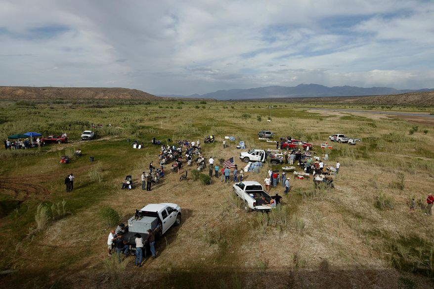 People gather along the Virgin River during a rally in support of Cliven Bundy near Bunkerville, Nev. Friday, April 18, 2014. (AP Photo/Las Vegas Review-Journal, John Locher)