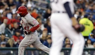 Los Angeles Angels' Howie Kendrick, back left, rounds the bases after hitting a two-run home run as Detroit Tigers starting pitcher Drew Smyly, right, walks on the mound during the third inning of a baseball game in Detroit, Friday, April 18, 2014. (AP Photo/Carlos Osorio)