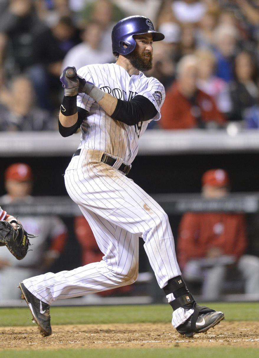 Colorado Rockies' Charlie Blackmon watches the flight of his RBI-single against the Philadelphia Phillies during the seventh inning of a baseball game on Friday, April 18, 2014, in Denver. (AP Photo/Jack Dempsey)