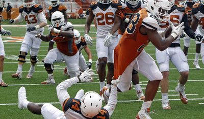 Texas running back Malcolm Brown (28) rushes for a touchdown against Chevoski Collins (14) during the first half of the Orange and White spring NCAA college football game on Saturday, April 19, 2014, in Austin, Texas. (AP Photo/Michael Thomas)