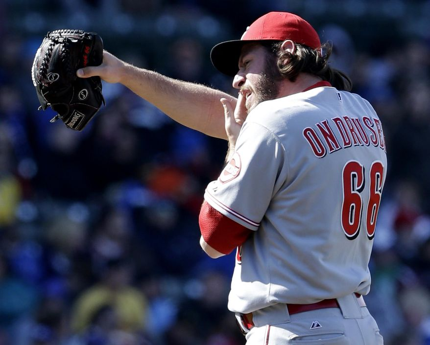 Cincinnati Reds relief pitcher Logan Ondrusek reacts as he wipes his face during the sixth inning of a baseball game against the Chicago Cubs in Chicago, Saturday, April 19, 2014. (AP Photo/Nam Y. Huh)