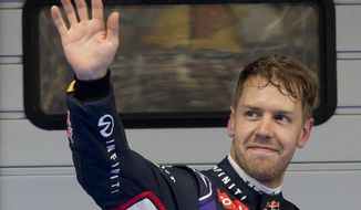 Red Bull Racing driver Sebastian Vettel of Germany waves to his fans after the qualifying session of the Chinese Formula One Grand Prix at Shanghai International Circuit in Shanghai, Saturday, April 19, 2014. Vettel takes third position for Sunday's Chinese Formula One Grand Prix race. (AP Photo/Andy Wong)